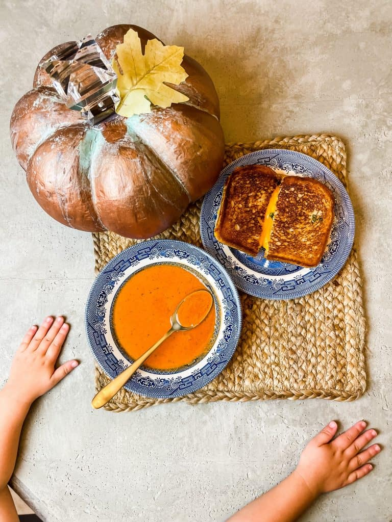 The best creamy tomato basil soup recipe with gourmet grilled cheese featured on my DIY concrete tabletop with my patina pumpkin decor.